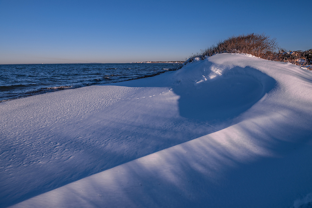 Curve of snow drift in sun & shadow, along beach in winter, with water views, Falmouth, MA