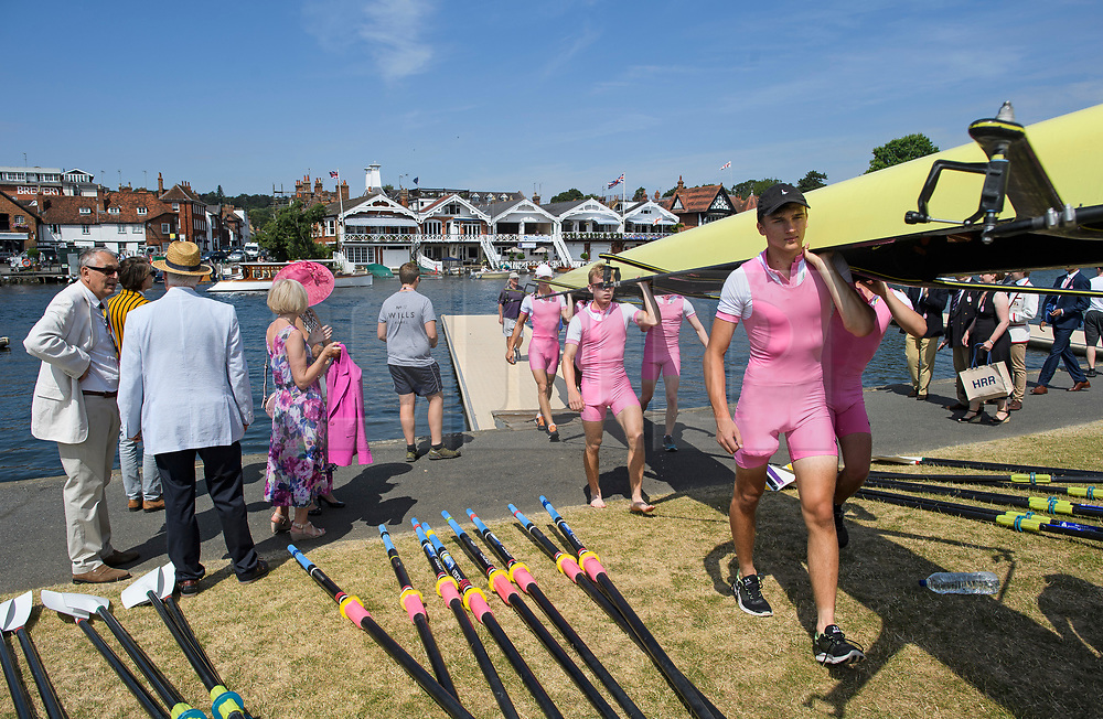© Licensed to London News Pictures. 04/07/2018. Henley-on-Thames, UK. A rowing team leaves the water on day one of the Henley Royal Regatta, set on the River Thames by the town of Henley-on-Thames in England. Established in 1839, the five day international rowing event, raced over a course of 2,112 meters (1 mile 550 yards), is considered an important part of the English social season. Photo credit: Ben Cawthra/LNP