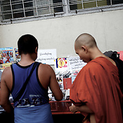 May 19, 2013 - Yangon, Myanmar: A buddhist monk buys goods at a CD stand marked with a sticker emblazoned with 969, the logo that has come to represent Myanmar's anti-Muslim movement. Taxis, buses, shop fronts and street stalls across the country display what some consider a symbol of Buddhist<br />extremism that sees Burma's Muslim community as a threat to the country and its dominant religion. (Paulo Nunes dos Santos/Polaris)