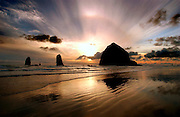Haystack Rock is silhouetted as the sun sets along Canon Beach in Oregon, USA, This portion of the Oregon coast is a favorite for many travelers, with it's unique typography.