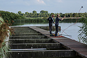 June 30, 2014 - Budel, Noord-Brabant, Netherlands - Two Dutch young men 'fishing' for metal throughout the artificial lakes of Noord-Brabant province in Netherlands. -This is the way we like to spend our weekend, fishing metals in the water- said Sonny, a Dutch young man on Sunday, June 30, 2014. (Credit Image: © Vedat Xhymshiti/ZUMA Wire)