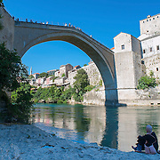 MOSTAR, BOSNIA AND HERZEGOVINA - JUNE 28:  Two Muslim girls are seen on the bank of the Neretva river under  the Old Bridge on June 28, 2013 in Mostar, Bosnia and Herzegovina. The Siege of Mostar reached its peak and more cruent time during 1993. Initially, it involved the Croatian Defence Council (HVO) and the 4th Corps of the ARBiH fighting against the Yugoslav People's Army (JNA) later Croats and Muslim Bosnian began to fight amongst each other, it ended with Bosnia and Herzegovina declaring independence from Yugoslavia.  (Photo by Marco Secchi/Getty Images)