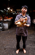 A man stands with a plucked chicken in Cho Hom Market, Hanoi, Vietnam