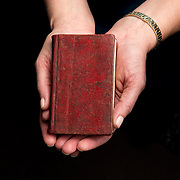 Luise Poulton, Rare Books Manager Special Collections  holds a copy of the Book of Commandments, a work written in 1830 by Joseph Smith and several other early Mormon leaders in the rare book collection at the J. Willard Marriott Library on the campus of the University of Utah in Salt Lake City, Utah Wednesday Oct. 10, 2012. (Photo by August Miller).