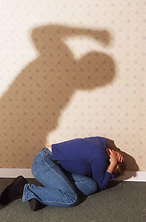 Young woman lying huddled on floor as abuser prepares to beat her,