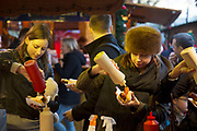 German bratwurst stall at the Christmas market doing a roaring trade as people queue for the grilled sausages and squeeze ketchup and mustard onto their food. The South Bank is a significant arts and entertainment district, and home to an endless list of activities for Londoners, visitors and tourists alike.