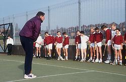 Games teacher teaching hockey to secondary school children on artificial pitch,