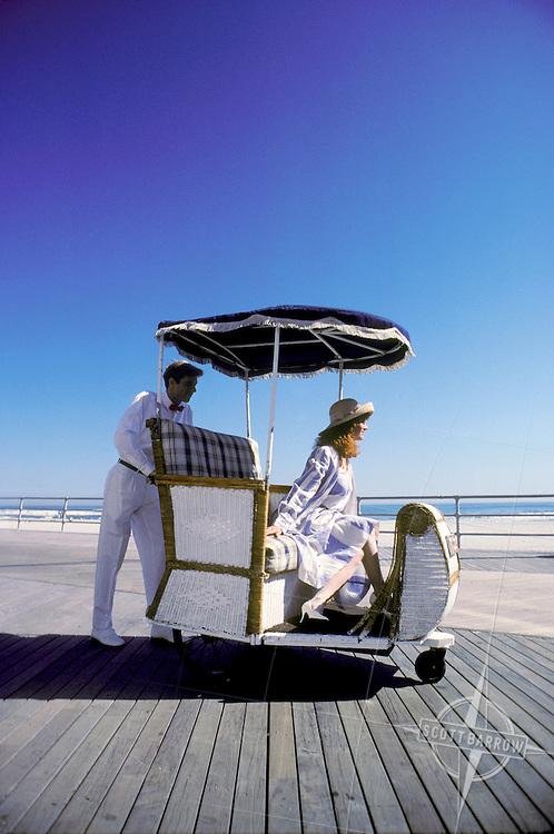 Red headed woman in hat enjoying a rolling chair ride on the boardwalk in Atlantic City, New Jersey.