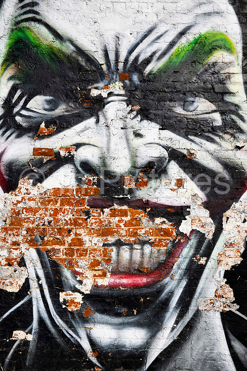 Street mural Street Artist Christian Fenn spent eight hours fighting against the elements to create this joker mural in Blackpool on 21st April 2021 in Blackpool, Lancashire, United Kingdom. The work was made for the Sun, Spray and Art, Blackpool`s Urban Art Festival.