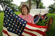 Patriotic memorabilia collector Carolyn West poses with a forty eight star American flag in the yard of the Roseland Plantation which was originally built in the 1840's. West, is an avid collector not only of flags but Victorian pickle dispensers, seed packets,Vegetable paitings,rose vases and all things pertaining to American patriotic iconography. Photo: Jaime R. Carrero/Tyler Morning Telegraph
