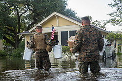 U.S. Marine Corps Sgt. Ben Tomerlin, left, a platoon sergeant, and Marine Gunnery Sgt. Jose Montoya, right, a utilities chief with the 14th Marine Regiment, 4th Marine Division, Marine Forces Reserves, walk supplies through a flooded street in Orange, Texas , Sept. 3, 2017. Hurricane Harvey landed in eastern Texas on Aug. 25, 2017, flooding thousands of homes and displacing over 30,000 people. (U.S. Marine Corps photo by Lance Cpl. Niles Lee)  Please note: Fees charged by the agency are for the agency's services only, and do not, nor are they intended to, convey to the user any ownership of Copyright or License in the material. The agency does not claim any ownership including but not limited to Copyright or License in the attached material. By publishing this material you expressly agree to indemnify and to hold the agency and its directors, shareholders and employees harmless from any loss, claims, damages, demands, expenses (including legal fees), or any causes of action or allegation against the agency arising out of or connected in any way with publication of the material.