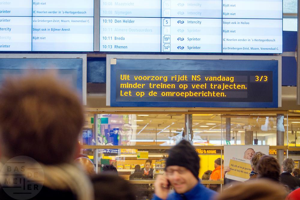 Reizigers op Utrecht CS kijken naar het informatiebord waarop te zien is dat veel treinen zijn uitgevallen of vertraagd. De eerste sneeuw in Nederland zorgt weer voor de nodige overlast. De NS heeft uit voorzorg de winterdienstregeling ingezet, waardoor veel minder treinen rijden.<br /> <br /> Passengers are looking at the information sign at Utrecht CS to see that lot of trains won't ride due to the snow in The Netherlands.