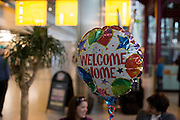 """A helium-filled Welcome Home balloon floats in the air in Heathrow Airport's Terminal 5 arrivals hall. Three families have gathered to meet their respective sons who have been travelling around the world during their university gap year sabbatical trip of a lifetime. Floating upwards, the balloon is brightly coloured amid the hectic concourse where other relatives greet their loved-ones after months away from home on their adventures. This is a tradition practised across the world's airports where families are separated by the need to travel or work in other countries and the emotion of meeting again after long absences is always hard. From writer Alain de Botton's book project """"A Week at the Airport: A Heathrow Diary"""" (2009)."""