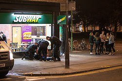 © Licensed to London News Pictures . 26/09/2017. Brighton, UK. Police detain , handcuff , bind the legs and put a hood over the head of a man outside a branch of Subway , after a fight in Steine Gardens in the Kemptown area of the city . Revellers at the end of a night out in Brighton during Freshers week , when university students traditionally enjoy the bars and clubs during their first nights out in a new city . Photo credit: Joel Goodman/LNP