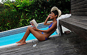 Girl reading by the pool at Strawberry Hill - Jamaica