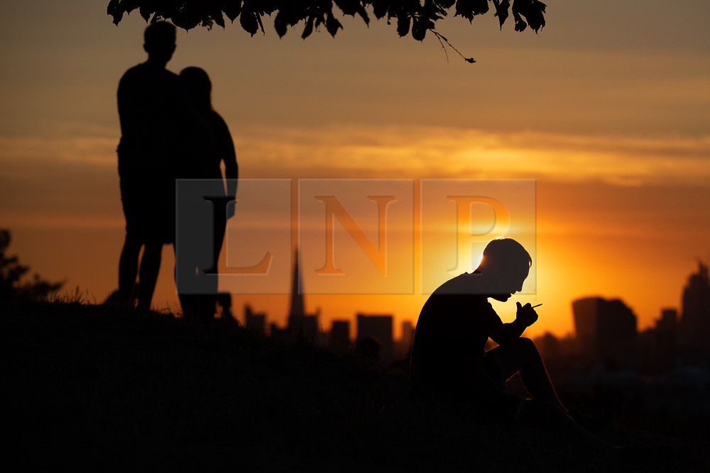 © Licensed to London News Pictures. 24/07/2018. London, UK. A couple watch the sunset over London's skyline as a man smokes a cigarette, after temperatures in the South East of England reached over 30 degrees celsius today. Temperatures are set to rise up to 35 degrees on Thursday, as the UK experiences a prolonged heatwave. Photo credit : Tom Nicholson/LNP