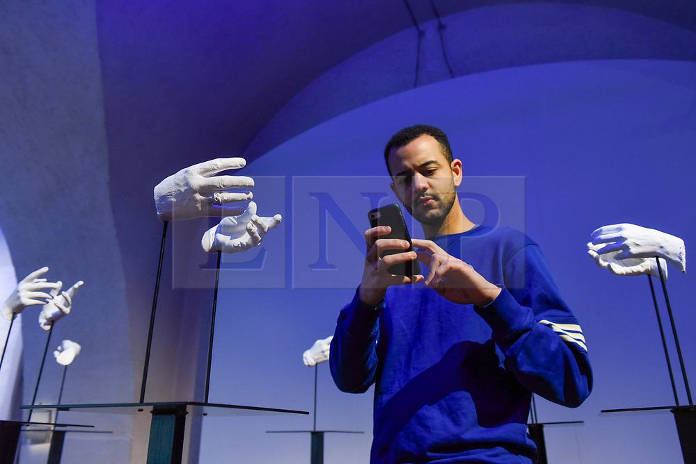"""© Licensed to London News Pictures. 29/10/2019. LONDON, UK. A staff member poses with """"Fifteen Pairs of Mouths"""", 2016-19, by Esmeralda Kosmatopoulos, plaster casts of hands which mimic the way hands text on a mobile phone. Preview of """"24/7: A Wake-Up Call For Our Non-Stop World"""", a new exhibition opening on 31 October at Somerset House.  The show examines our inability to switch off from our 24/7 culture.  Over 50 multi-disciplinary works explore the pressure to produce and consume information around the clock. taking visitors on a 24-hour cycle from dawn to dusk through interactive installations.  Photo credit: Stephen Chung/LNP"""