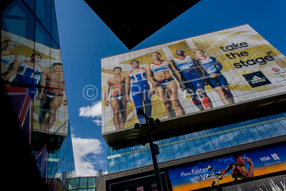 The giant presence of Team GB role-model athlete heroes on the side of the their HQ at the Westfield City shopping complex, Stratford that leads to the Olympic Park during the London 2012 Olympics, the 30th Olympiad. The ads are for Visa and for sports footwear brand Adidas and their 'Take the Stage' campaign including diver Tom Daley, gymnast Louis Smith and the darling of British athletics, heptathlete gold medallist Jessica Ennis. Situated on the fringe of the 2012 Olympic park, Westfield is Europe's largest urban shopping centre providing the main access to the Olympic park with a central 'street' giving 75% of Olympic visitors access to the main stadium so retail space.