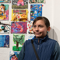 A young local artist MB Brown, 11, poses for photo ops near her abstract & collage work during the 15 in 30 challenge art show at the art123 Gallery in Gallup on Saturday.