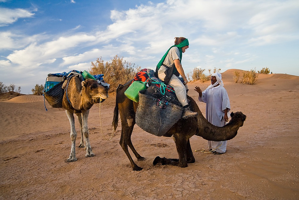 Elhussein Sbiti helps an American client dismount from a camel on a three-day trek to the remote dunes of Erg Zehar, near M'hamid in the Moroccan Sahara. Sbiti, like many berber nomads in the region, has found opportunity in the new tourism trade burgeoning since the settling of tensions between Morocco and neighboring Algeria.