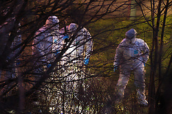 © Licensed to London News Pictures. 28/12/2011. Salford, UK. Forensic investigators continue to work in to the night looking for evidence following the murder of Indian student Anuj Bidve. They search through a small patch of wasteland on the corner of Ordsall Lane and Asgard Drive, in bushes and through trees, by torchlight. The 23 year old Lancaster University student was shot on Boxing Day. Photo credit : Joel Goodman/LNP