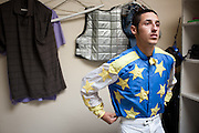 © Steven St. John / The Communicator..Jude Baca watches the first race on TV while getting dressed before his race at The Downs at Albuquerque on Friday, Sept. 2, 2011.....