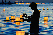 A videographer is silhouetted filming the Lantern Floating Ceremony is Ala Moana Beach Park.