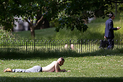© Licensed to London News Pictures. 15/06/2021. London, UK. A man sunbathes during sunny weather in St James's Park in Central London. Temperatures are expected to rise with highs of 25 degrees forecasted for parts of London and South East England today . Photo credit: George Cracknell Wright/LNP