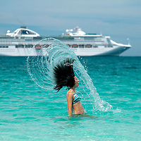 A girl takes a dunk in the perfect, transparent water of Isle of Pines, New Caledonia.