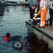Gestolen auto, Opel Corsa, gevonden in de aanloophaven Huizen, duikers van de brandweer bergen het wrak