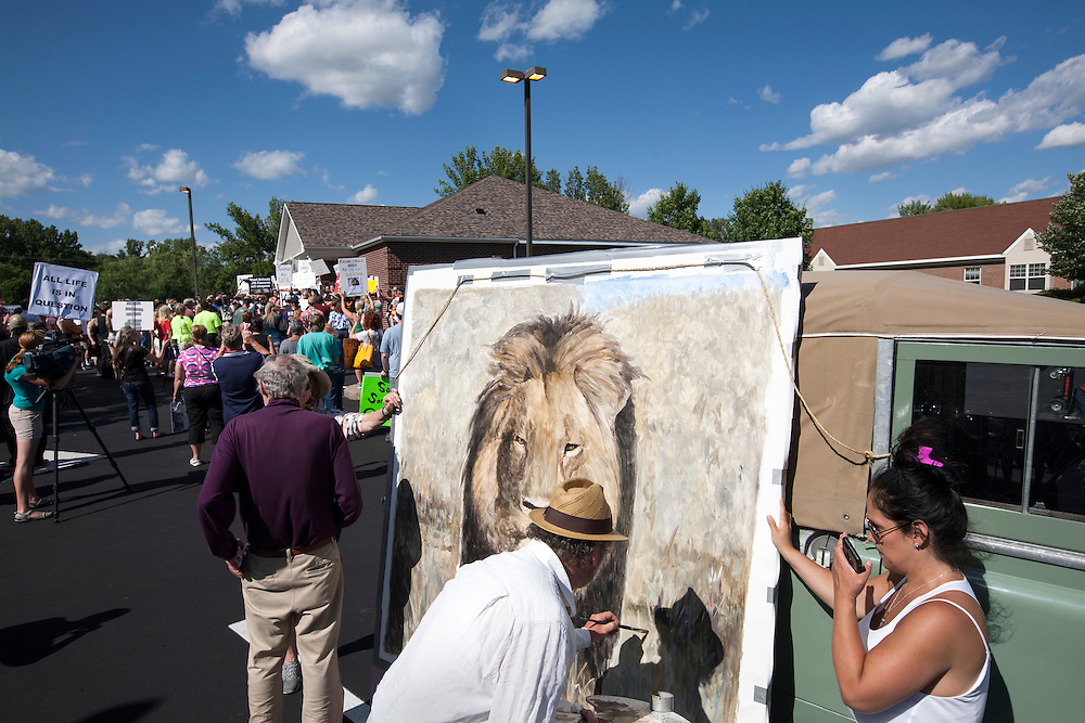 Artist Mark Balma who splits his time between Italy and California finished his lion painting during a protest at the dental office of Walter James Palmer in Bloomington, MN, July 29, 2015.  Balma grew up in the Twin Cities and happened to be in town when the Cecil news broke.  His painting will be auctioned off to raise money for the protection of wildlife.