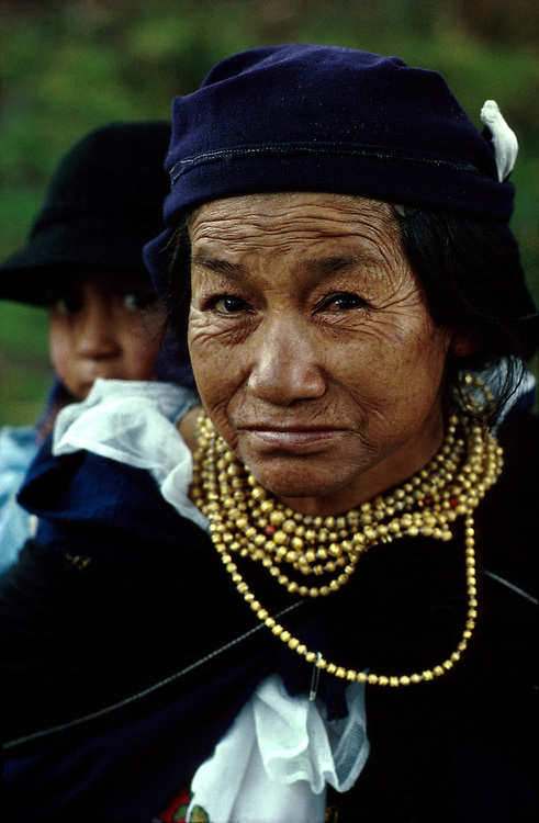 Otavalan mother and daughter. The mother wears the traditional blue and gold beads of the proud Otavalan Indians.