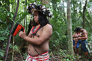Surui indians using Timbtrack technology inside Surui territory primary rainforest interior.<br /><br />An Amazonian tribal chief Almir Narayamogo, leader of 1350 Surui Indians in Rondônia, near Cacaol, Brazil, with a $100,000 bounty on his head, is fighting for the survival of his people and their forest, and using the world's modern hi-tech tools; computers, smartphones, Google Earth and digital forestry surveillance. So far their fight has been very effective, leading to a most promising and novel result. In 2013, Almir Narayamogo, led his people to be the first and unique indigenous tribe in the world to manage their own REDD+ carbon project and sell carbon credits to the industrial world. By marketing the CO2 capacity of 250 000 hectares of their virgin forest, the forty year old Surui, has ensured the preservation, as well as a future of his community. <br /><br />In 2009, the four clans and 25 Surui villages voted in favour of a total moratorium on logging and the carbon credits project. <br /><br />They still face deforestation problems, such as illegal logging, and gold mining which causes pollution of their river systems