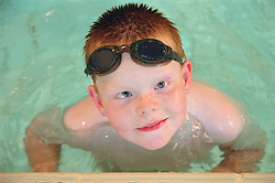 Young boy with Cerebral Palsy swimming in public swimming pool,
