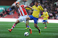 Arsenal's Lukas Podolski holds off  Stoke's Geoff Cameron. Barclays Premier league, Stoke city v Arsenal match at the Britannia Stadium in Staffordshire, England on Saturday 1st March 2014.<br /> pic by Andrew Orchard, Andrew Orchard sports photography.