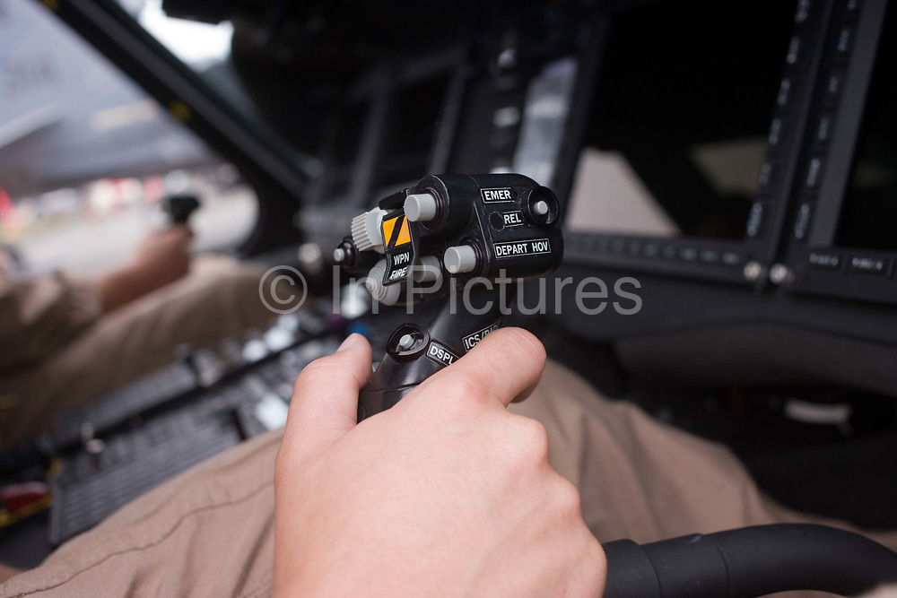 US Navy pilot grasps cyclic in the cockpit of a Sikorsky MH-60R helicopter at the Farnborough Airshow. The MH-60R is the U.S. Navy's newest and most advanced multi-mission helicopter, designed for anti-submarine and surface warfare (ASW/ASuW). Secondary missions include: Search and Rescue, anti-ship surveillance and targeting, communication relay and medevac/vertical replenishment. The Sikorsky-built helicopter with integrated avionics and mission systems by Lockheed Martin.