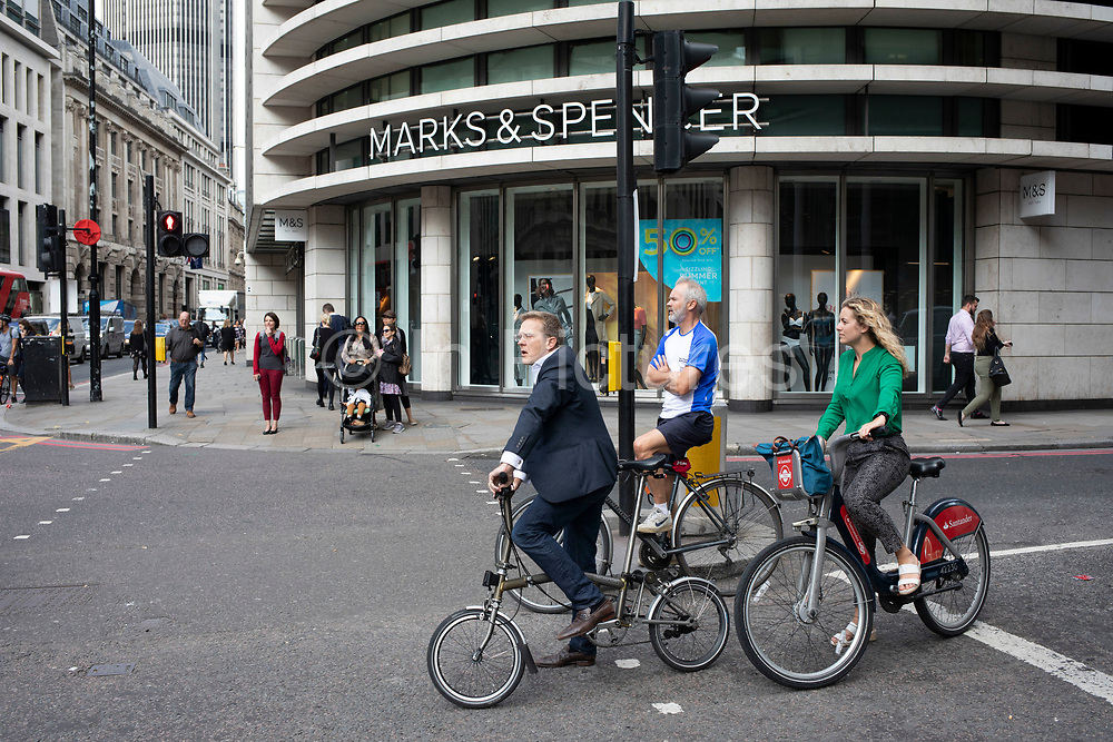 Street scene with different cyclist commuters waiting at the traffic lights in the City of London, England, United Kingdom. Cycling has become a very popular mode of transport in the capital as people try to avoid public transport, saving money, getting fit and saving time.