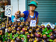10 JULY 2018 - NAKHON PATHOM, THAILAND:  A woman sells mangosteens in the market in Nakhon Pathom. Nakhon Pathom is about 35 miles west of Bangkok. It is one of the oldest cities in Thailand, archeological evidence suggests there was a settlement on the site of present Nakhon Pathom in the 6th century CE, centuries before the Siamese empires existed. The city is widely considered the first Buddhist community in Thailand and the nearly 400 foot tall Phra Pathom Chedi is considered the first Buddhist temple in Thailand.    PHOTO BY JACK KURTZ