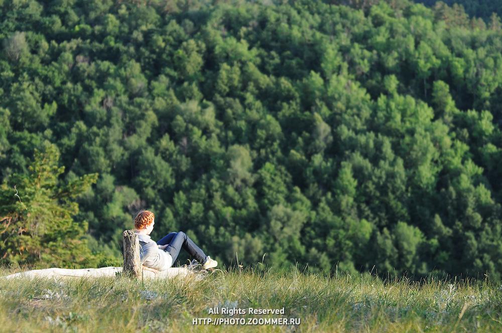 "Girl sitting on a high hill near the steep in Russian National Park ""Samara Luka"""