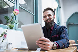 Smart businessman using digital tablet while sitting at cafÈ