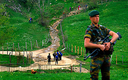 Children walk home from school under the protection of KFOR NATO peace keeping forces in the Albanian muslim village of Bare, in Northern Kosovo. The soldier said if the peace keeping forces left the area that these people would most likely be attacked by Serbs in nearby villages. (Photo © Jock Fistick)