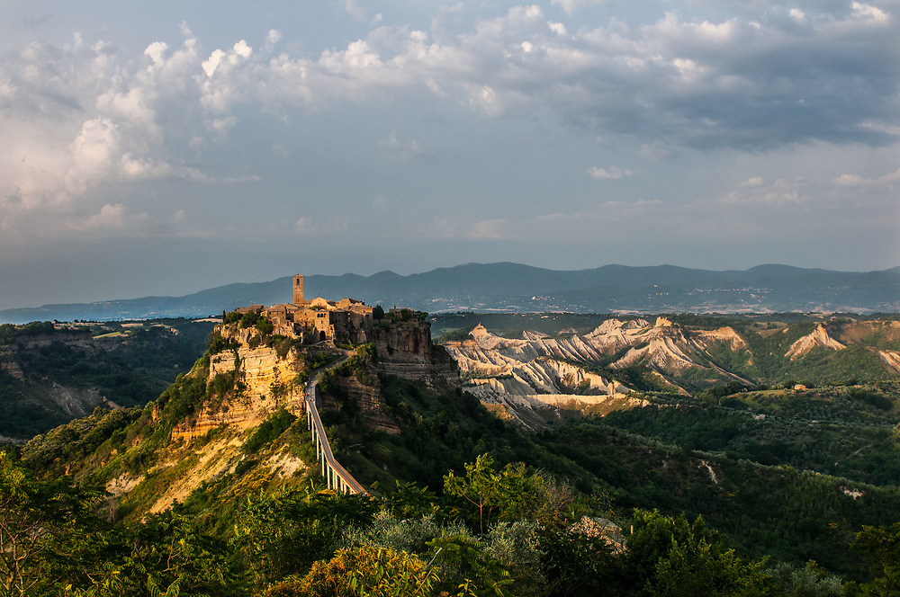 """A panoramic view of the village of Civita di Bagnoregio.<br /> Civita di Bagnoregio is a town in the Province of Viterbo in central Italy, a suburb of the comune of Bagnoregio, 1 kilometre (0.6 mi) east from it. It is about 120 kilometres (75 mi) north of Rome. Civita was founded by Etruscans more than 2,500 years ago. Bagnoregio continues as a small but prosperous town, while Civita became known in Italian as La città che muore (""""The Dying Town""""). Civita has only recently been experiencing a tourist revival. The population today varies from about 7 people in winter to more than 100 in summer.The town was placed on the World Monuments Fund's 2006 Watch List of the 100 Most Endangered Sites, because of threats it faces from erosion and unregulated tourism."""