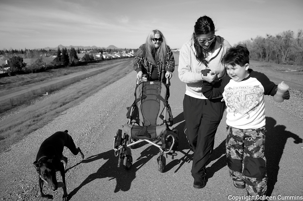 Mary McGinnis, 51, left, and her grandson Alex Acuna,8, right, walk along the levee at in Yuba City with respite worker Gloria Peralta, 26, in preparation for the upcoming protest walk to the state capital in February of 2011. Mary began to organize within the disabled community a march from her home, 40 miles from the state capital, under the name Mommy Tsunami. <br /> <br /> In the winter of 2010 Mary, driven by California's budget cuts began to fear that the Lanterman Act, a 1977 state law, that provides the developmentally disabled with the right to services, allowing them to live more independent would be stripped. Mary began to organize within the disabled community a march from her Yuba City home, 40 miles from the state capital, under the name Mommy Tsunami. Many folks who are caregivers for a disabled family member depend on these hours to get a well deserved break from the round the clock care they provide to their loved ones.