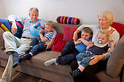 Ottersland Dahl family, of Gjettum, Norway (outside Oslo). The grandparents watch cartoons with the grandchildren, Olav, 6 Hakon, 3, and Sverre, 1.5 in their basement TV room.