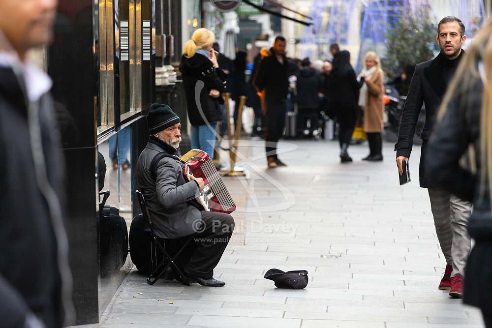 A street Musician plays his accordion on Bond Street, just off Oxford Street. Homeless Britons are coming under increasing pressure as a surge of Roma beggars from Romania arrive on the streets of London to take advantage of the generosity of Christmas shoppers. London, December 04 2018.