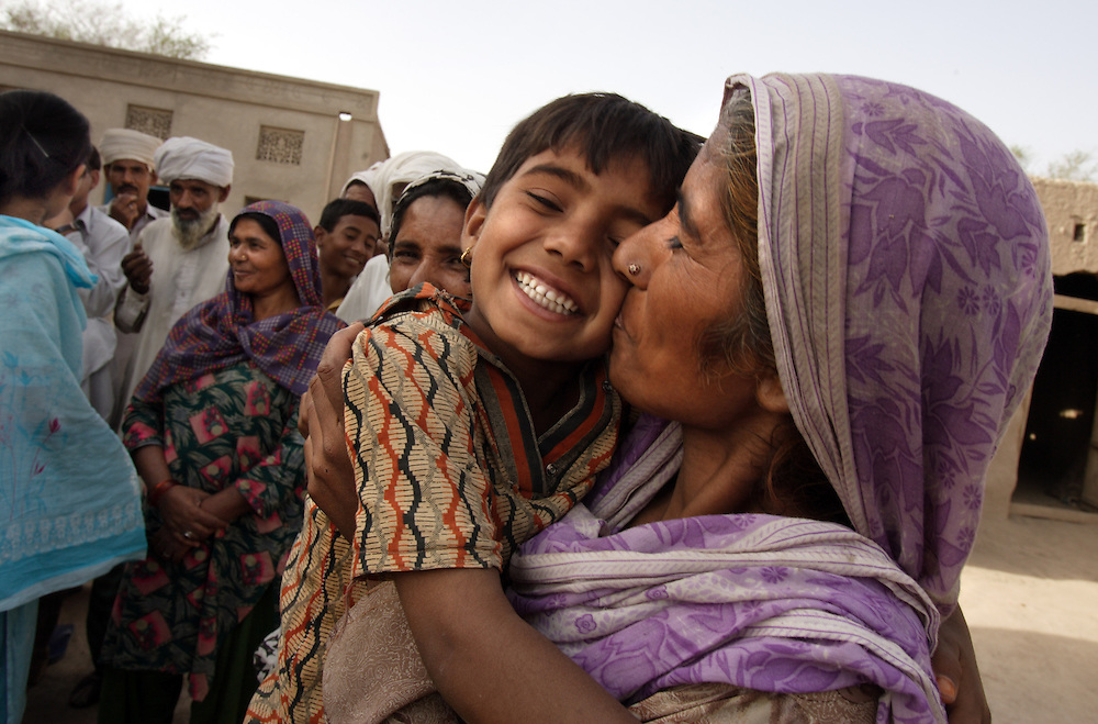 """Tasleem, kisses daughter Rafiabibi, 6, as social worker Asia Perveen, in blue, talks to relatives, Dera, Pakistan, April 26, 2005. Perveen speaks about Tasleem and her sister Zubada's  potential case against the neighbors who gang raped them when they felt they were dishonored by Zubada's son Naeem. Members of the Human Rights Commission in Multan, including Perveen, are working with the women to get them legal representation so they can fight the accusers in court. """"I want them to be punished,"""" said Tasleem. """"They are our enemies, I will be afraid until they are hanged publicly."""""""