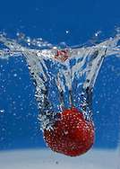 A strawberry takes a plunge into sparkling water.