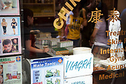 Scene in London's famous Chinatown around Gerrard Street. Window of a Chines herbal medicine shop. Advertising for Viagra and masage is prominent.