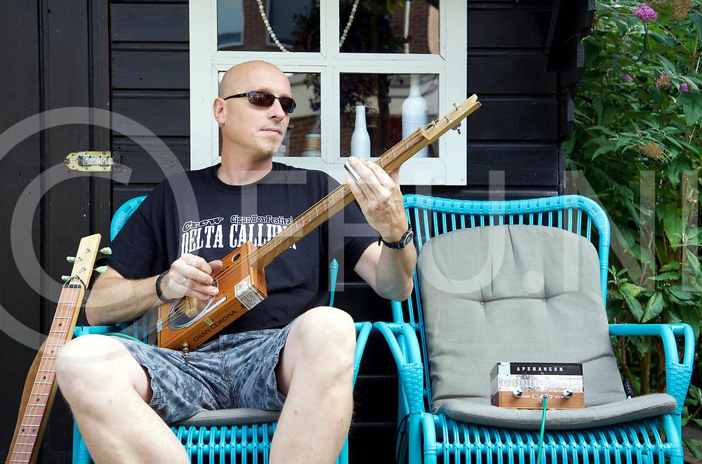 DALFSEN - Cigar box festival.<br /> Foto:  Henri Grootenhuis speelt op een  Cigar box gitaar voor het tuin huisje.<br /> Let op details als een verstekerker van een sgarenbox.<br /> FFU Press Agency copyright Frank Uijlenbroek