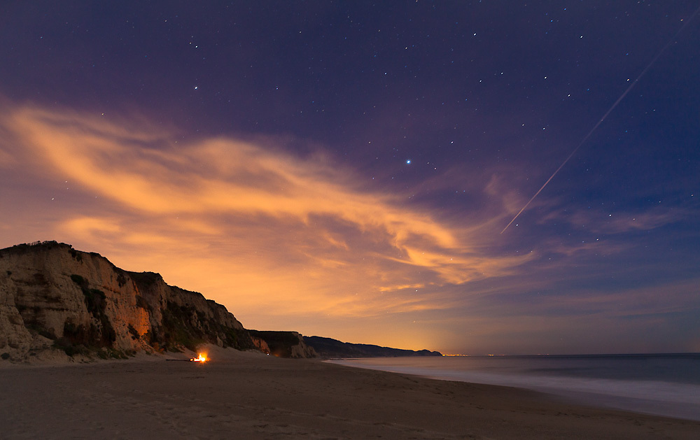 An airplane flies past stars and over campfires, heading toward the light of San Francisco to the south.